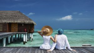 Couples on a tropical beach jetty at Maldives_tropical_sky